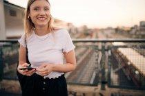 Ritratto di giovane donna sorridente che tiene lo smart phone in piedi sul ponte in città — Foto stock