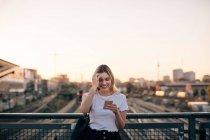 Усміхаючись молоду жінку, використовуючи смарт-телефону на мосту проти чистого неба під час заходу сонця в місті — стокове фото