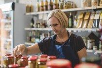 Employé féminin arrangeant des bocaux dans la deli — Photo de stock