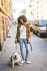 Ritratto di donna adulta sorridente in piedi con cane sul marciapiede in città — Foto stock