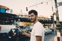 Портрет молодий чоловік тримає мобільного телефону, поки стоїть по тротуару в місті — стокове фото