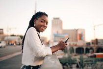 Side view portrait of young woman holding mobile phone while standing on bridge in city — Stock Photo
