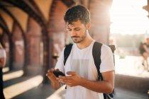 Giovane utilizzando il telefono cellulare mentre in piedi sul sentiero in città — Foto stock