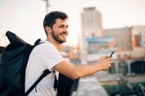 Вид сбоку улыбающийся молодой человек, глядя удерживая мобильный телефон на мосту — стоковое фото