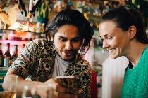 Sorrindo jovem compartilhando telefone inteligente com a mulher sentada no restaurante durante a festa de brunch — Fotografia de Stock