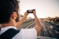Giovane uomo fotografare attraverso il telefono cellulare su binari ferroviari in città — Foto stock