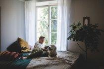 Toute la longueur du livre de lecture de l'homme retraité tout en se reposant avec le chien sur le lit à la maison — Photo de stock