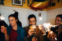 Young multi-ethnic male and female friends holding burning sparklers in restaurant during dinner party — Stock Photo