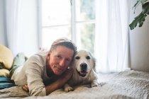 Portrait en gros plan d'un homme et d'un chien âgés allongés sur leur lit à la maison — Photo de stock