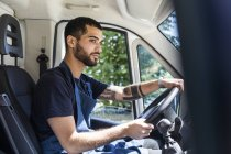 Vue latérale du jeune propriétaire masculin confiant conduisant un camion de nourriture en ville — Photo de stock