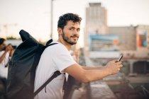 Стороні подання портрет молодий чоловік тримає мобільного телефону під час спершись на перила на мосту — стокове фото