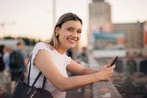 Ritratto di giovane donna sorridente che tiene il telefono cellulare mentre si appoggia sulla ringhiera al ponte in città — Foto stock
