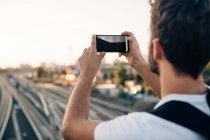 Giovane uomo fotografare attraverso smart phone su binari ferroviari in città — Foto stock