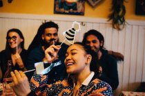 Jovem alegre segurando adereços enquanto se senta contra amigos multi-étnicos no restaurante durante o jantar — Fotografia de Stock