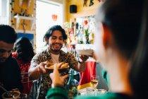 Homem novo de sorriso que dá o alimento à mulher ao sentar-se pelo amigo na tabela no restaurante durante o partido do brunch — Fotografia de Stock