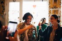 Uomo fotografare allegri giovani amici alzando brindisi celebrativo al ristorante durante il brunch — Foto stock