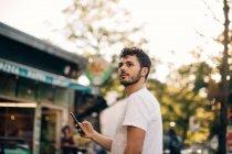 Вид сбоку молодого человека, глядя стоя на улице в городе — стоковое фото