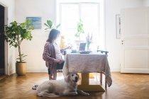 Собака сидит женщина, завтракающая за столом во время работы из дома — стоковое фото