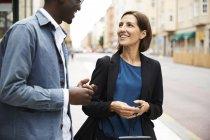 Усміхнені чоловіки і жінки пасажири говорять, стоячи на тротуарі в місті — стокове фото