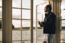 Homme mûr réfléchi utilisant le téléphone portable tout en se tenant à la porte dans la villa de vacances — Photo de stock