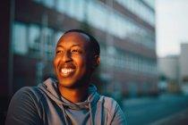 Крупный вид улыбающегося молодого человека, отворачивающегося в городе — стоковое фото