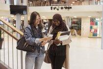 Lächelnde Schülerin zeigt Smartphone zu Freundin, während im Flur an der High School stehen — Stockfoto