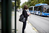 Side view of businesswoman standing on sidewalk waiting at bus stop in city — Stock Photo