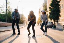 Joven bailando con amigos varones en la calle en la ciudad - foto de stock