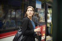 Femme d'affaires confiante regardant loin tout en se tenant avec un verre contre le bus en ville — Photo de stock