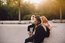 Jovem mulher atenciosa segurando telefone celular enquanto se senta com os amigos no parque de skate — Fotografia de Stock
