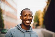 Gros plan portrait d'un jeune homme souriant en ville — Photo de stock