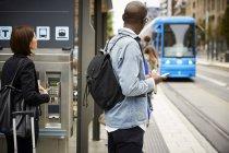 Los viajeros se paran en la acera mientras esperan el tranvía en la ciudad - foto de stock