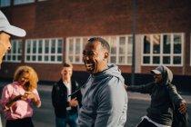 Jeune homme gai dansant avec des amis dans la ville le jour ensoleillé — Photo de stock