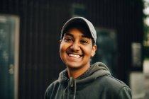 Ritratto di uomo sorridente che indossa berretto e camicia con cappuccio in città — Foto stock