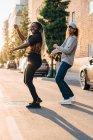Comprimento total de amigos sorridentes dançando na estrada na cidade — Fotografia de Stock