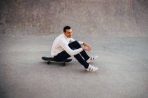 Comprimento total do homem sorridente sentado no skate no parque — Fotografia de Stock