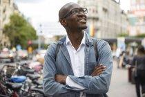 Sonriente hombre de negocios de medio adulto mirando hacia arriba mientras está de pie con los brazos cruzados en la ciudad - foto de stock