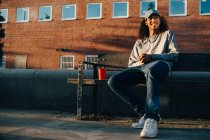 Homem feliz olhando para longe enquanto sentado no banco contra o edifício — Fotografia de Stock