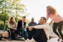Femme de sourire poussant l'homme sur la planche à roulettes tandis que les amis heureux s'asseyant au stationnement — Photo de stock