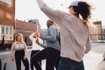 Amici allegri multietnici che ballano per strada in città — Foto stock