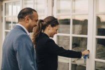 Smiling mature couple unlocking glass door at holiday villa — Stock Photo