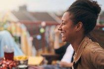 Vista lateral da jovem alegre que gosta de festa no terraço — Fotografia de Stock