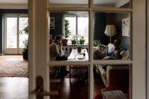 Famille utilisant diverses technologies dans le salon vu à travers la porte transparente à la maison — Photo de stock