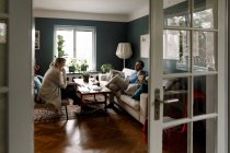 Family using various technologies in living room seen through doorway at home — Stock Photo