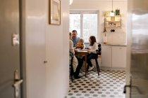 Familia comiendo juntos en la cocina en casa - foto de stock