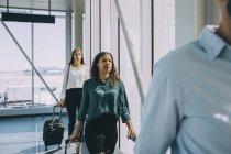 Fila de colegas de negócios multi-étnicos andando no corredor no aeroporto — Fotografia de Stock
