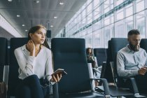 Thoughtful young businesswoman looking away while sitting by colleague at waiting area in airport — Stock Photo