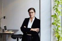 Retrato de empresária madura confiante apoiando-se na parede no escritório — Fotografia de Stock