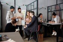 Kreative Geschäftsleute diskutieren über Projekt mit Bankmanagern im Büro — Stockfoto