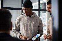 Homme entrepreneur tenant tablette numérique tout en étant debout par un collègue lors d'une réunion dans le bureau créatif — Photo de stock